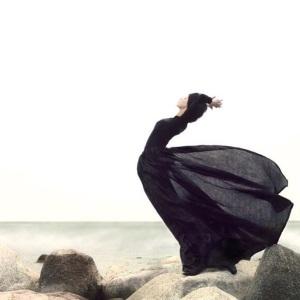 buigen in de wind  vrouw aan zee windvangen